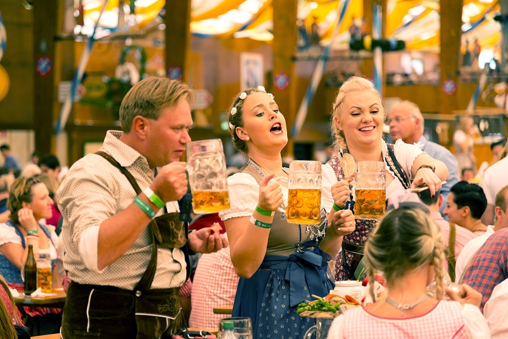 Munich, Germany - September 29, 2016: Oktoberfest in Munich, Germany. A group of young people in beer hall, celebrating Oktoberfest on Theresienwiese. People are dressed in traditional clothes and holding beer glass. The Oktoberfest is the largest fair in the world and is held annually in Munich.
