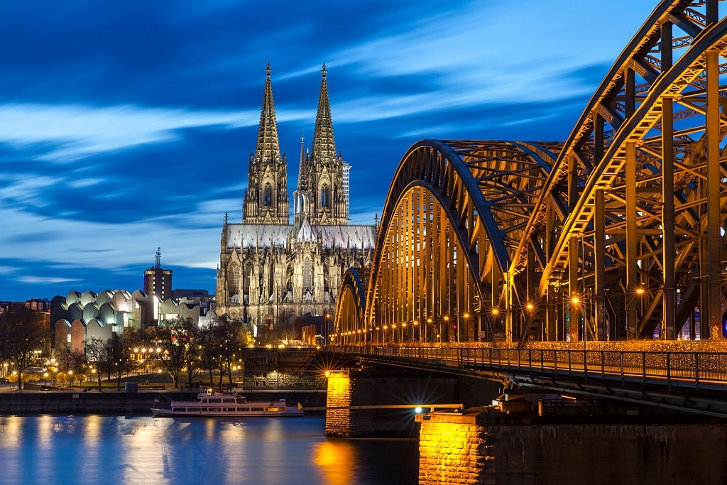 Cologne Cathedral with Hohenzollern Bridge at night.